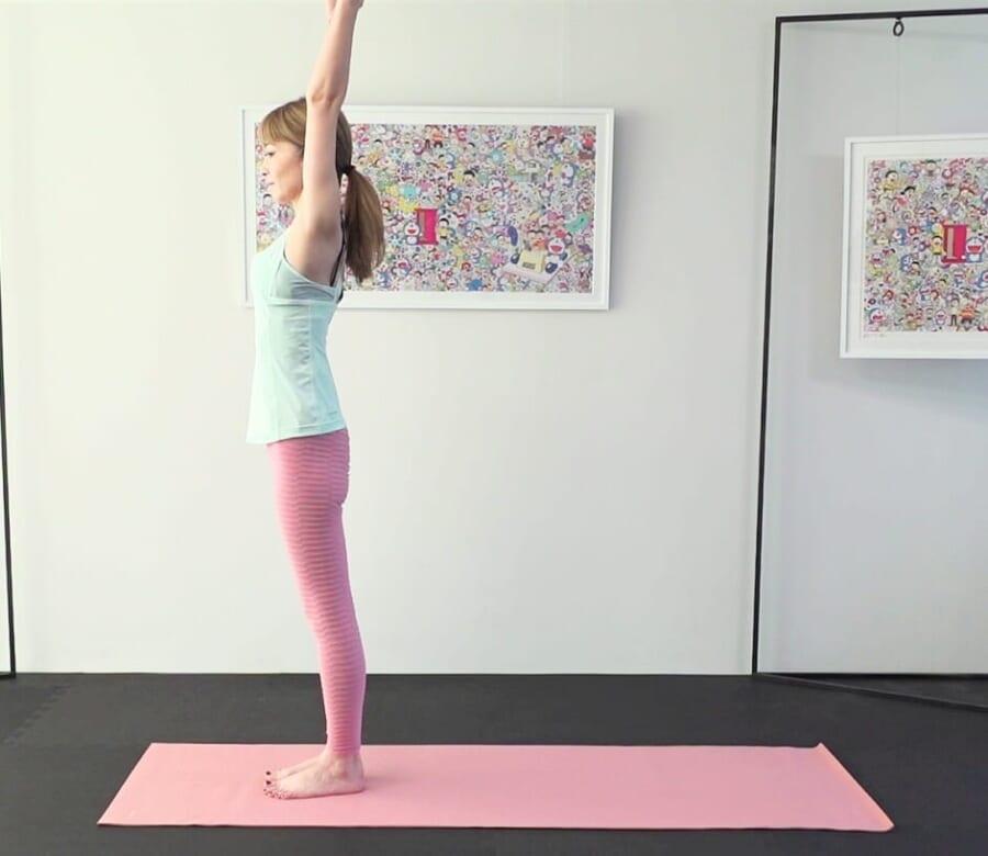 足は腰幅(握りこぶし2つくらい)に開き、お腹を腰に引き寄せ背骨を伸ばします。腰が反らないようにお腹への意識を高めながら、両手を上に伸ばします。