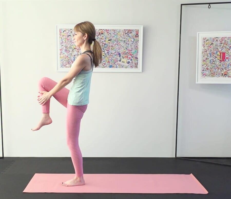 左かかとで床を押し、吸う息で右脚を引き上げ両手でつかみます