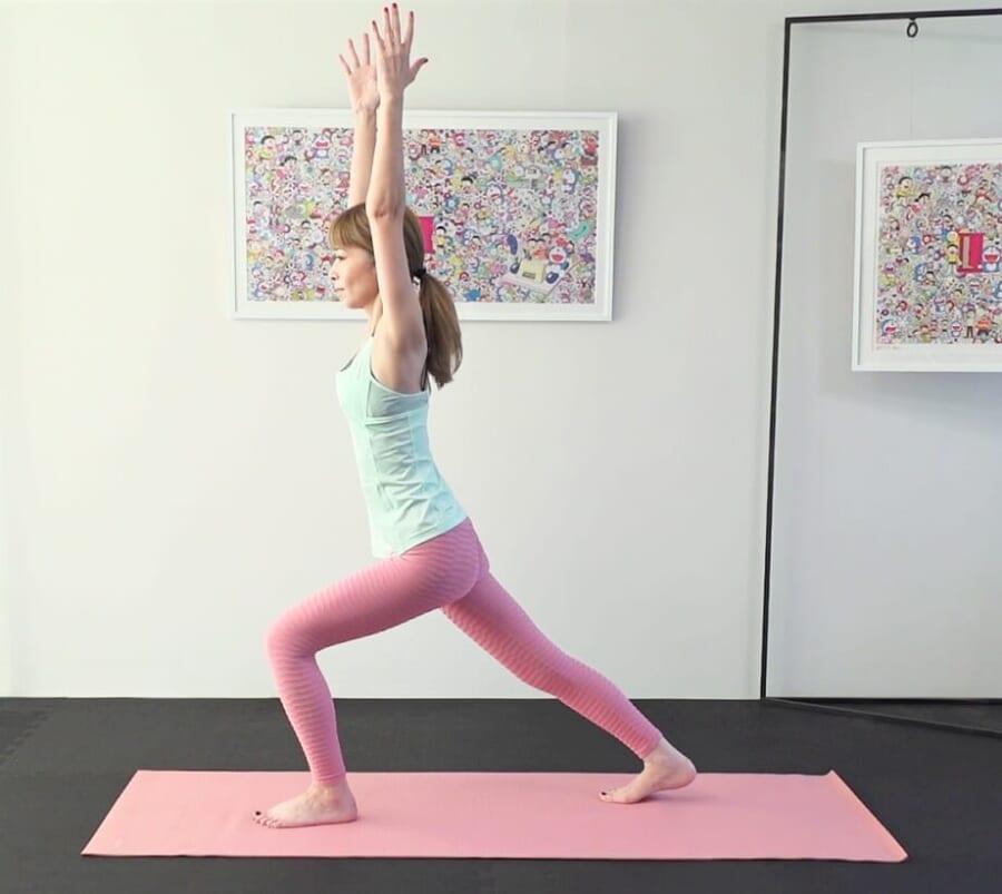 息を吐きながら右つま先を後ろに伸ばして床につけ、ハイランジ(足を前後に大きく開き、両手を天井方向に上げる)の形になります。この時も、腰が反ったり丸まったりしないように体幹の安定性を意識してください。後ろ脚は後ろに押し出すようにして、膝が落ちないように注意しましょう