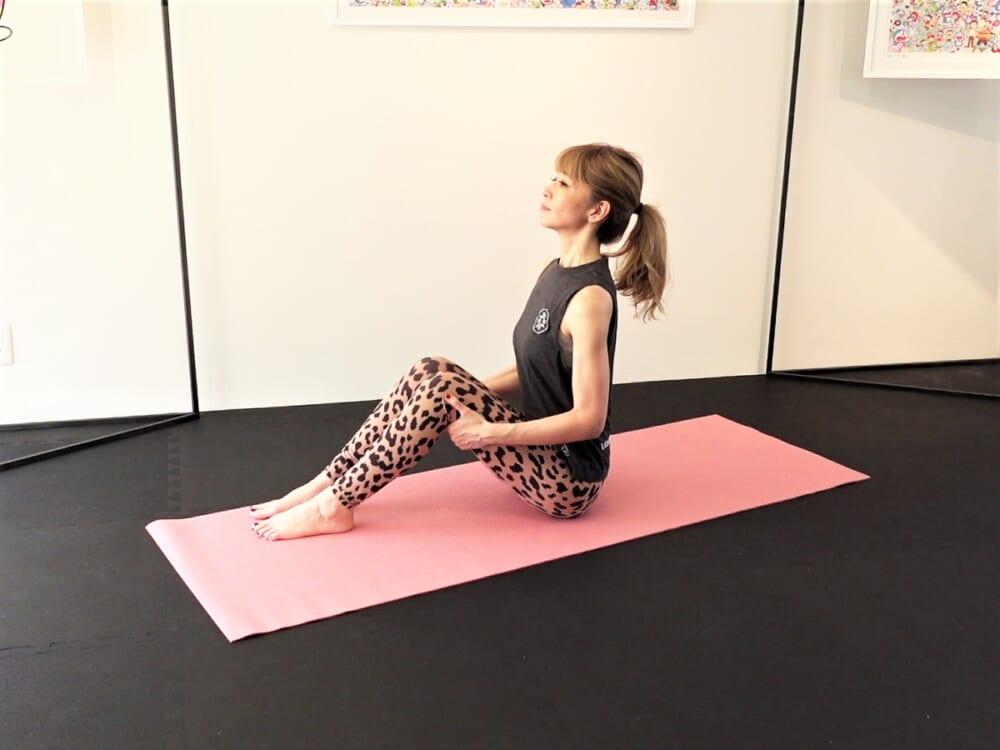 床に体育座りのように座ります。お尻のムダ肉をかきわけて、坐骨(お尻の丸い2つの骨)を床につけます。足幅は握りこぶし1つくらい開き、おへそと胸を正面に向けます。