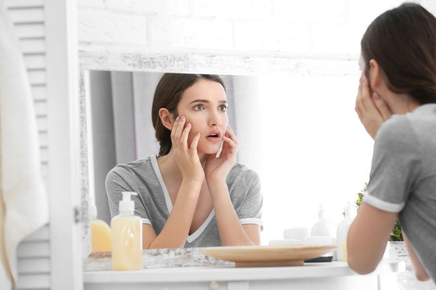 鏡の前で毛穴に悩む女性