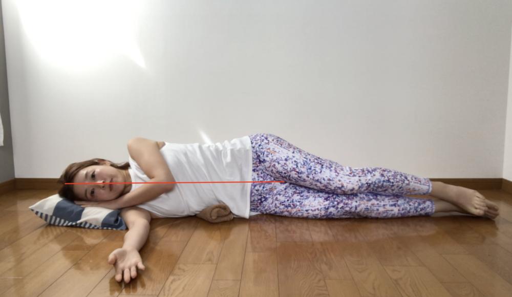 写真のように横向きに寝た時に背骨が一直線になるように頭には枕、ウエストのくびれのところにタオルを敷きます。下側の手は前に伸ばし、上側の手はラクな位置におきましょう