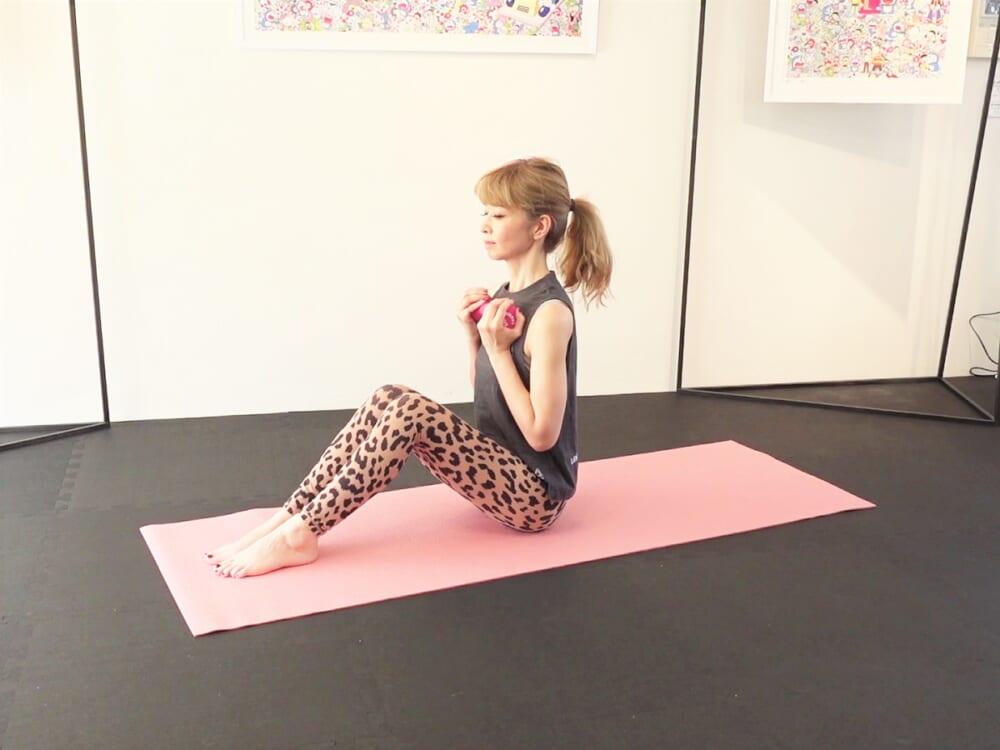 体育座りになり、膝を90度曲げて両膝を閉じます。ダンベルを胸の前に置き、吐く息と共にお腹を腰に引寄せ姿勢を整えます