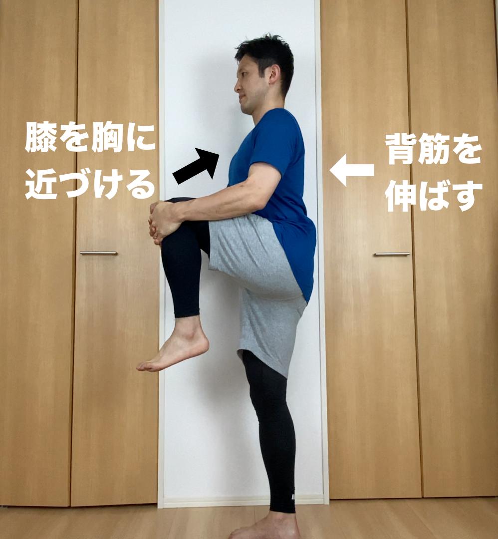立った姿勢からスタートします。左脚を上げて両手で左膝を抱え、背筋を真っ直ぐに伸ばします