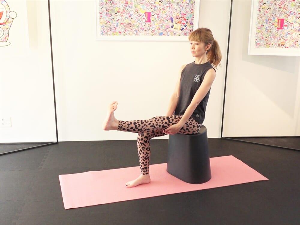 膝の真下に踵がくるように椅子に浅めに腰かけます。左脚を前に伸ばし膝頭、太ももをギュッと力を入れまっすぐ伸ばします。両手は太もも裏にそえて、吐く息と共にお腹を腰に引寄せドローイングして姿勢をキープしてください