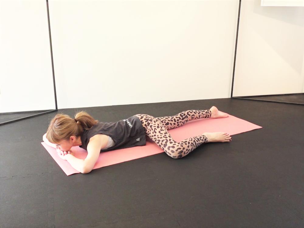 うつ伏せになり、恥骨を床につけます(つかない人は猫背姿勢が習慣化して、腰痛になりやすくなっているかもしれません)。両手を重ねて顎を乗せ、脚の付け根を直角に曲げます