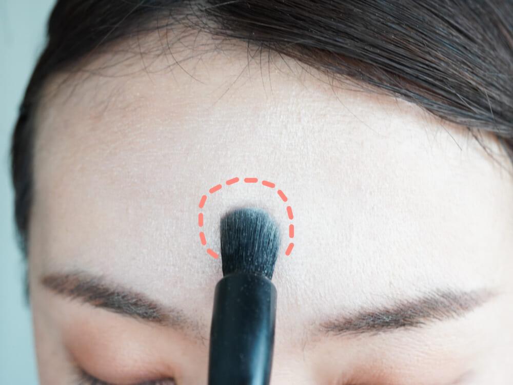 パウダーハイライトを毛の密度が高い細めのブラシ(もしくは指の腹)にとり、おでこの高い部分にポイント的に入れます