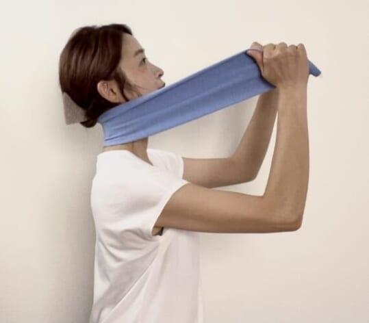 首にタオルをかけたら、タオルの両端を手で持ってタオルをやさしく前方に引っ張ります。首を後ろに少し倒して20秒キープします