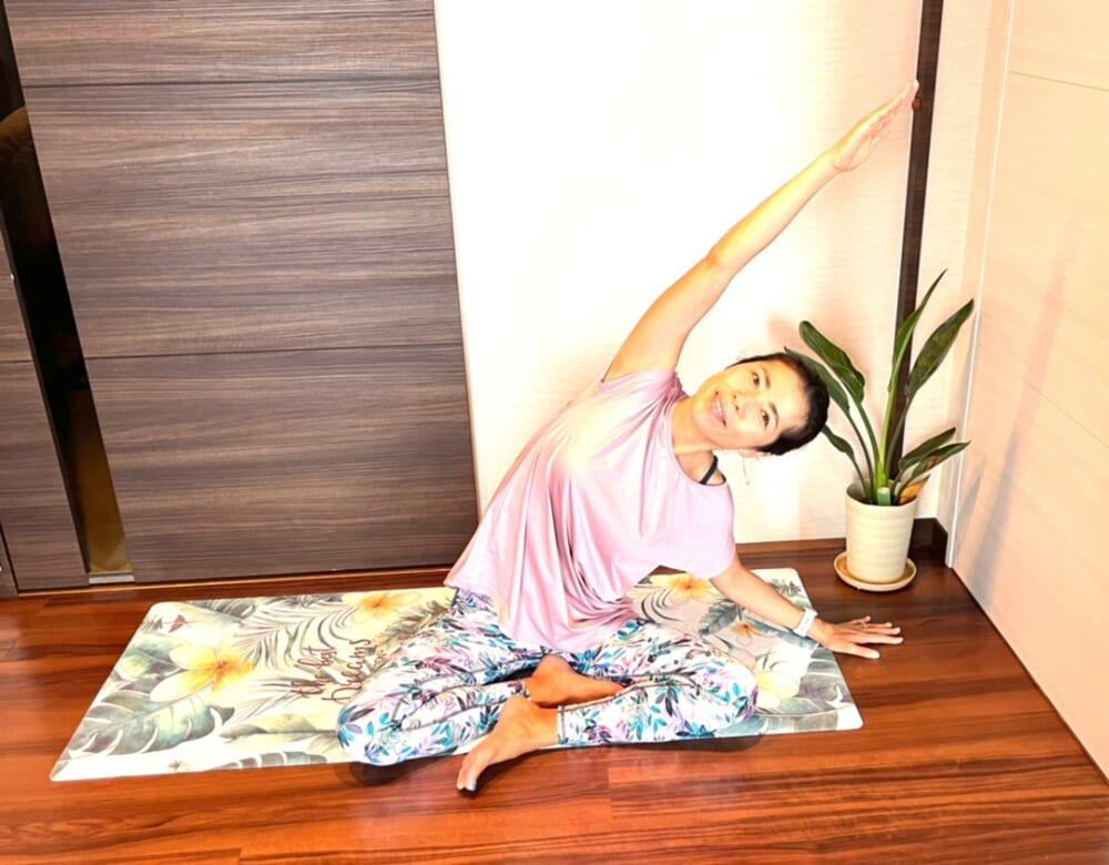 あぐらの姿勢で座り、息をゆっくり深く吸いながら両腕を横に開きます。息をゆっくり吐きながら、片手を床に置き反対側の腕を体側を伸ばすように横から斜め遠くに伸ばします