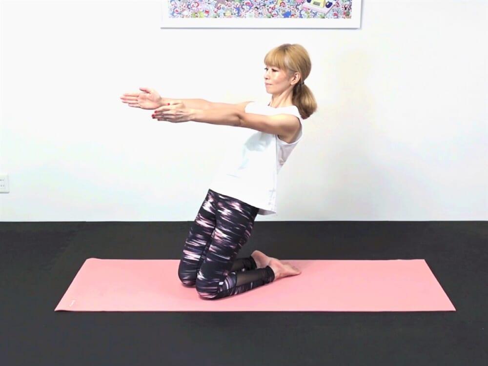 次に、両手を前に伸ばして肩を下げ、体幹を安定させます。吐く息とともに上体を後ろに傾け、吸う息とともに元の位置に戻る動作を3回繰り返します。戻る時にお腹にシワが寄らないように注意してください