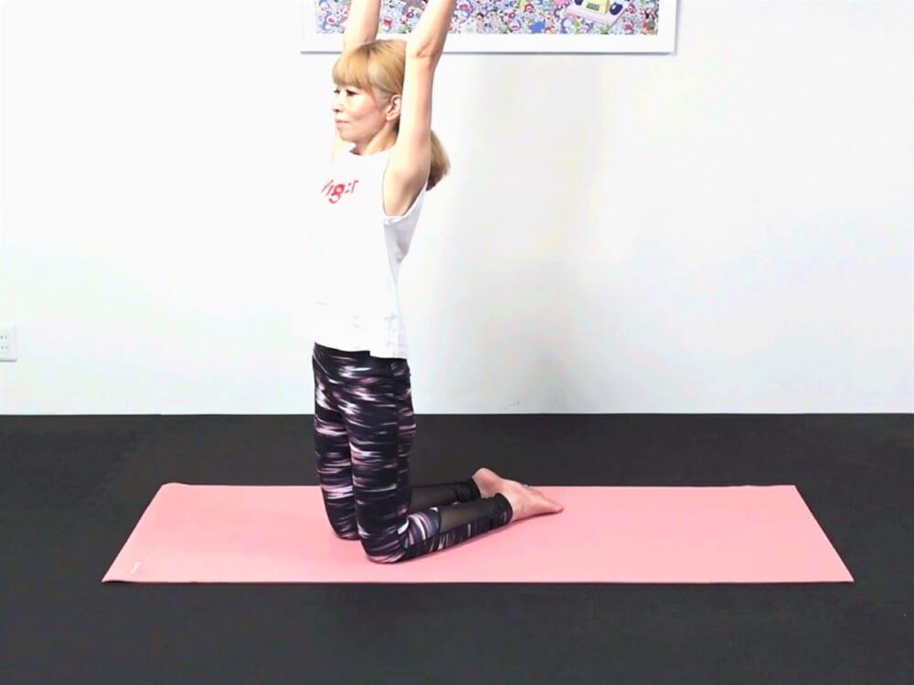 両手を天井方向に伸ばします。この時、お腹と腰を引寄せたまま上体の姿勢が変わらないように注意してください