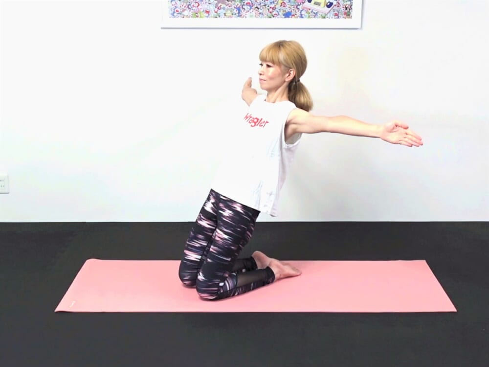 吐く息とともに両手を肩の高さにおろしながら上体を後ろに傾け、さらに両手を肩の高さに広げます。吸う息とともに元の位置に戻ります。これをもう一度繰り返してください