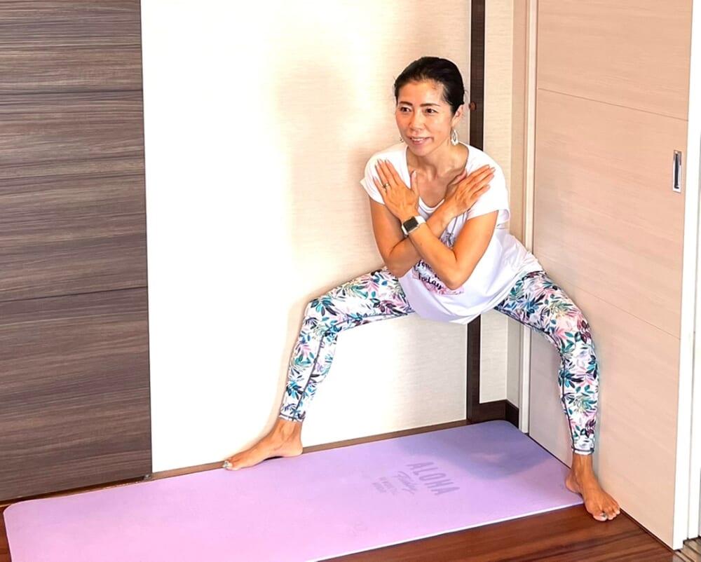 息を吸いながら膝を曲げて、お尻を後ろに引きます。この時、膝とつま先の方向が同じになるように(膝が内側に向かない)、両脇の壁に膝がきちんとつくのを確認しながら行うことがポイントです