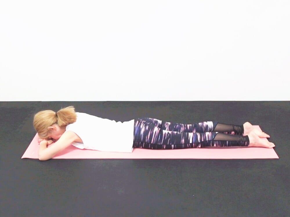 うつ伏せ姿勢になり、重ねた腕に額を乗せてゆっくりと呼吸を繰り返します。胸、あばら、恥骨を床につけて身体の前側をストレッチさせましょう