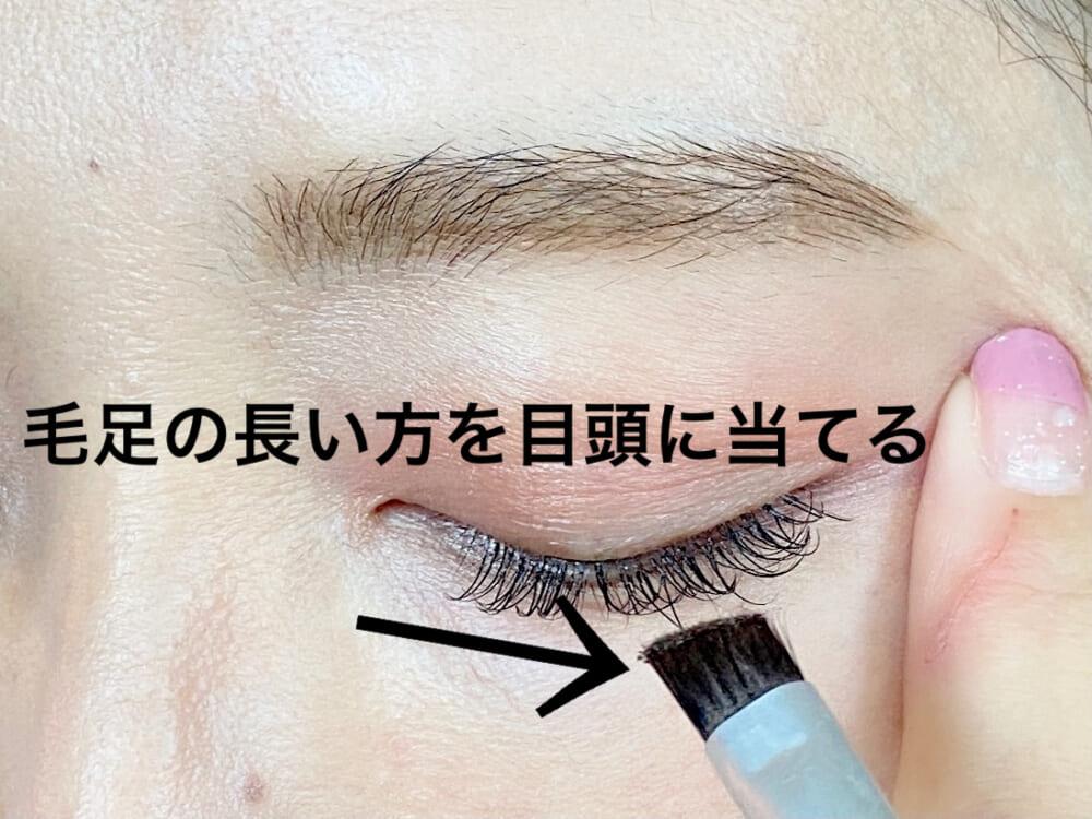 アイブロウブラシの毛先だけに締め色をつけて、片方の手で目尻を軽く抑えます。目頭にアイブロウブラシの長い面が当たるようにします。
