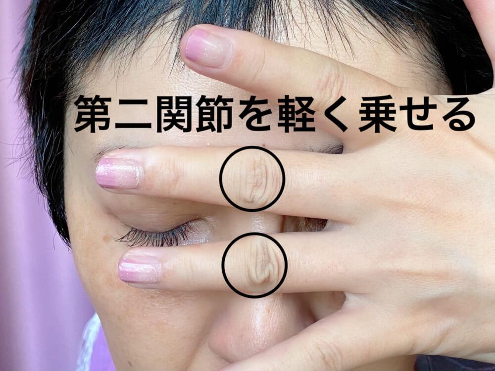 中指と薬指の第二関節を眉間と鼻骨の中央にそっと置きます