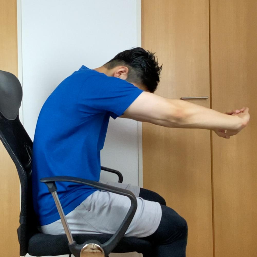 両手を組み手のひらを前にして腕を伸ばし、背中を丸めます。この時、息を吐きながら、肩甲骨を外側に押し出すようなイメージで行ってください