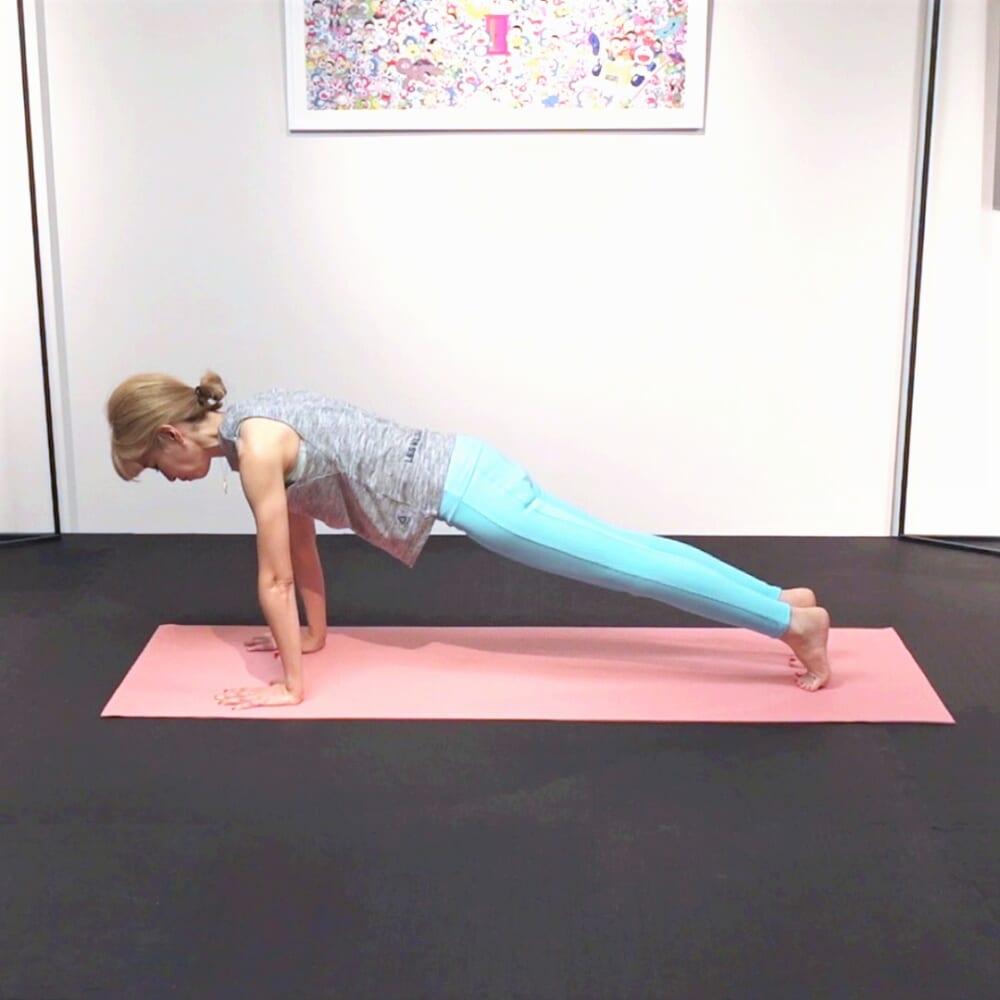 両手を肩幅に広げ、プランクポジションを作ります。お腹を腰に引き寄せ、体幹を安定させてください。あごを軽く引き、肩甲骨を脚の付け根方向に下げると、さらに体幹が安定します